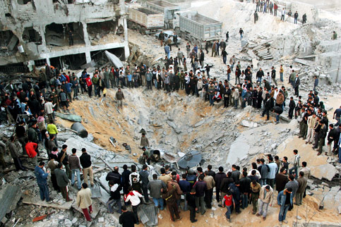 Palestinians gather around a crater caused by an Israeli air strike in the northern Gaza Strip. (Mohamed Al-Zanon/MaanImages)