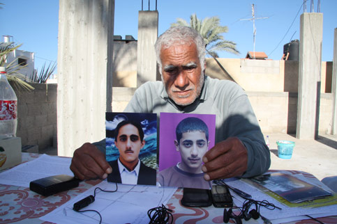 Muhammad Shurrab holds pictures of his son Kassab (left) and Ibrahim, killed during Israel's siege of Gaza. (Reem Salahi)