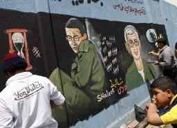 Hamas members painting the Gilad Shalit mural Wednesday
